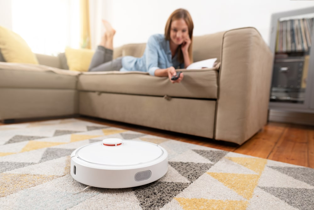 Robotic vacuum cleaner cleaning the with woman relaxing on the sofa