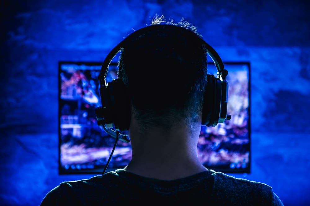 man playing Xbox while wearing a headset