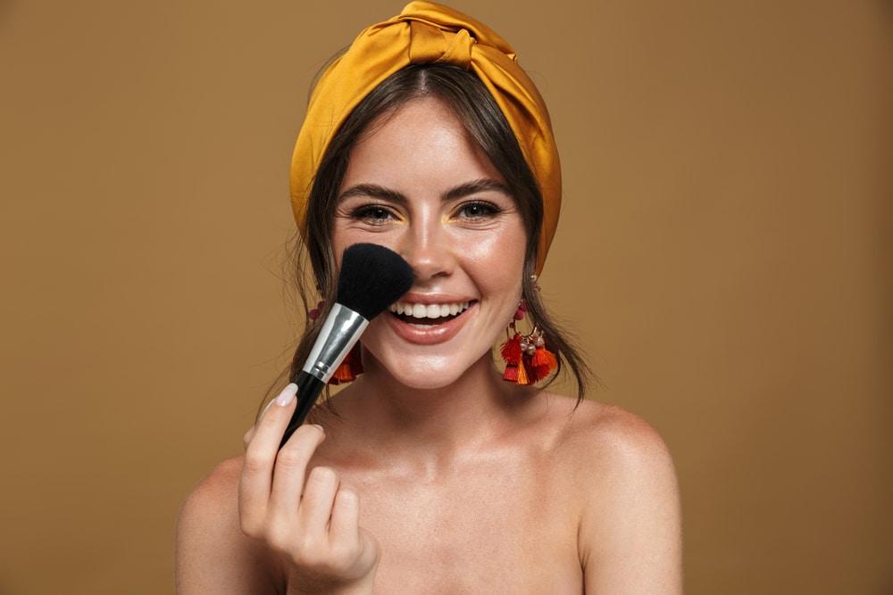 beautiful woman applying foundation