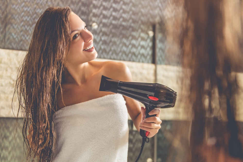 woman uses hair dryer
