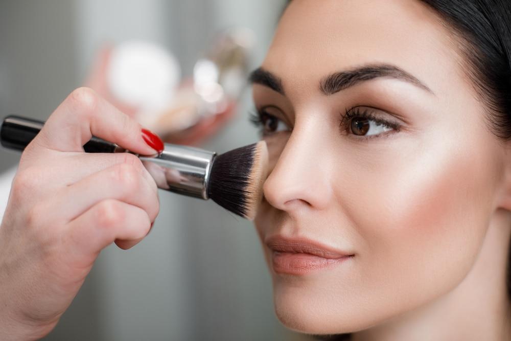 woman applying highlighter makeup