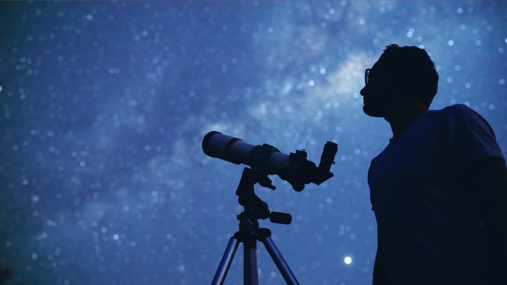 man watching stars with telescope